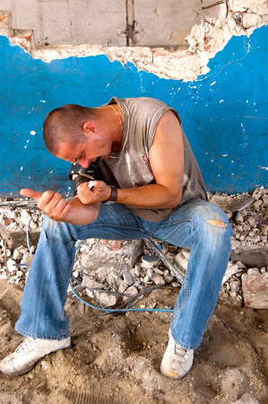 drug addict: Drug addict injecting himself in the gloomy basement Stock Photo