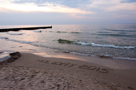sea landscape with a beautiful setting sun and the inscription on a beach vacation.