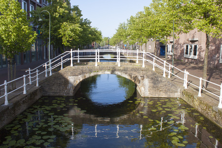 bridge over canal with reflection and trees photo