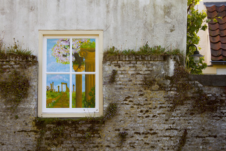 painted window on stone wall with moss Standard-Bild