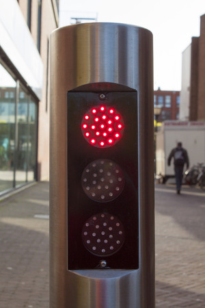 red traffic light on silver tube with black background