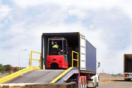 forklift: Semi truck backed onto loading ramp