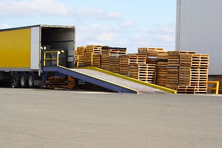 Semi truck backed onto loading ramp and stack of pallets