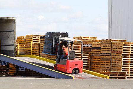 Forklift driver loading truck photo