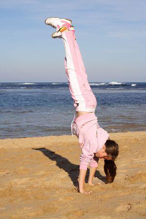 Girl doing handstand on beach photo