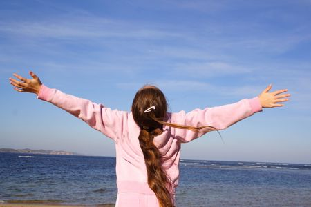 Girl with open arms at beach photo