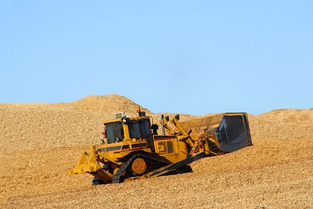 Earth mover driving on wood chips photo