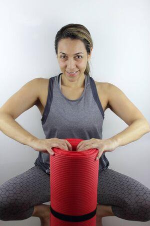 Beautiful active woman with her yoga mat Фото со стока