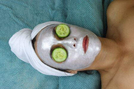 Beautiful Woman with face mask and cucumber eyes