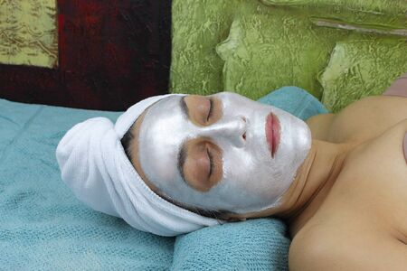 Beautiful Woman with face mask and a towel