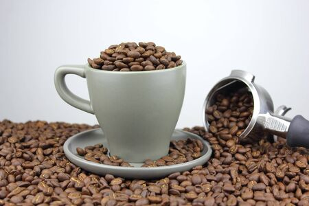 Coffee beans in a cup and saucer with a group handle