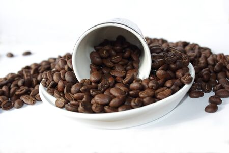 Dark roasted coffee beans in a cup and saucer