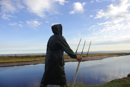 The person with a trident representing the sea god on seacoast. Stock Photo