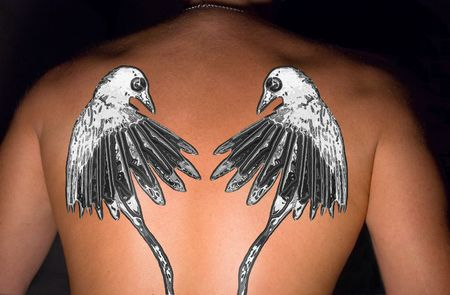 joining forces: Tattooed magpies  on a back of the sportsman. A collage