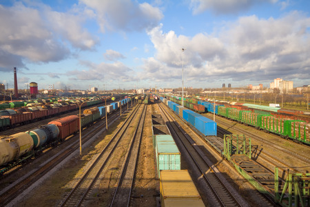 Freight train with color cargo containers passing railway station Imagens