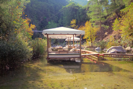 cuisine entertainment: Tables of  restaurant are among  pure river in  mountains. Clear water and reflection. Editorial