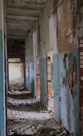 pitfall: long corridor in a crumbling brick building Stock Photo