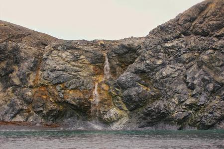 homogeneous: Cliffs, composed of shale. Small summer waterfall. Barents sea, Novaya Zemlya