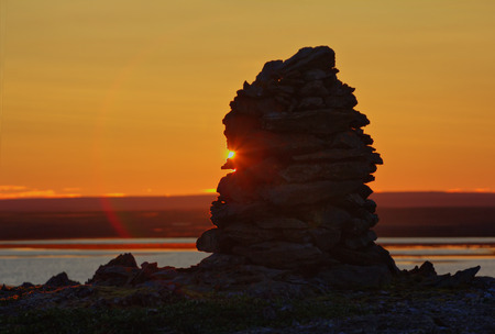 saami: Old cairn in Arctic wilderness photographed against background of sunset sky. Not setting sun (behind cairn) of polar day Stock Photo