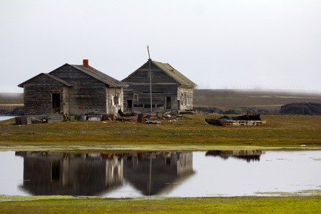 polar station: The wooden buildings of old pole station. Buildings are reflected in quiet water of lagoon