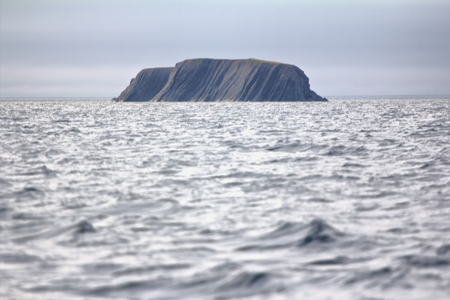 monte cristo: Layered Rock in sea pierced by waves and wind. Arctic ocean