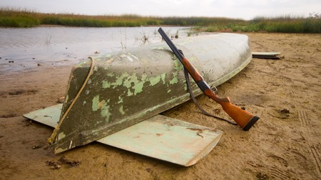 undemanding: main equipment of ducks hunter - canoe and shotgun Stock Photo