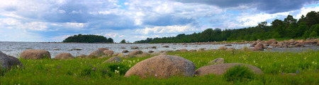 erratic: Sea shore with huge erratic boulders and lush green meadow Stock Photo