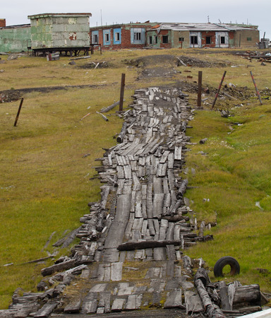 land use: abandoned village in the Russian Arctic and wood road Stock Photo