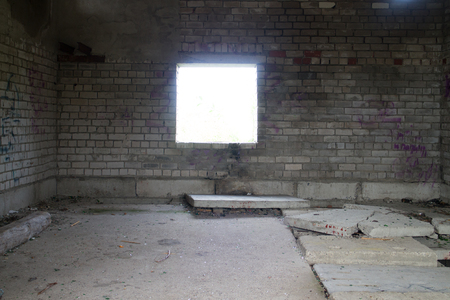 abandoned room: spacious abandoned empty room with brick wall and window Stock Photo