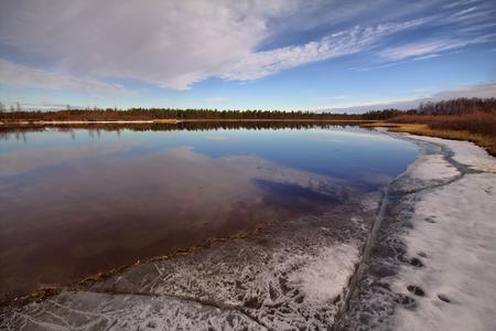 educacion ambiental: fundir estanque con agua tomada de un punto bajo. Cerca de la nieve. Foto de archivo