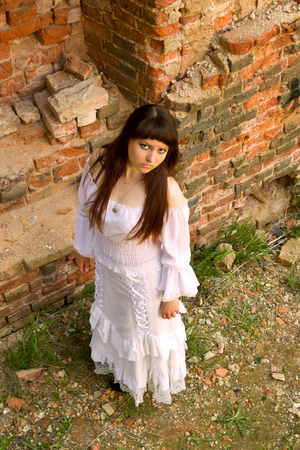 girl in a ball gown among the ruins of antiquity. white clothes on a young girl on brick wall background