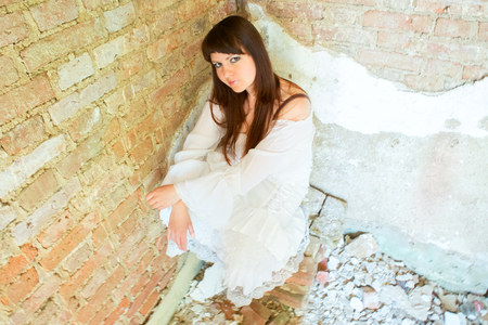gullible: girl in white dress sitting in corner. pose and look in a limited space