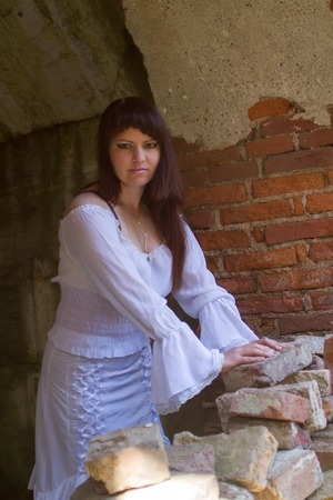 arduous: girl in a ball gown among the ruins of antiquity. white clothes on a young girl on brick wall background