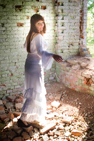 impassioned: girl in a ball gown among the ruins of antiquity. white clothes on a young girl on brick wall background