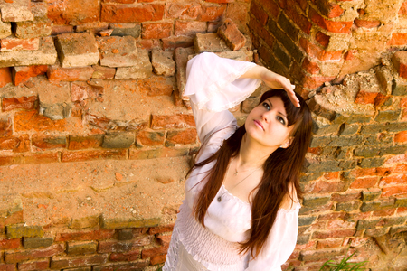 nonchalant: Girl in old-fashioned white dress among ruins of old manor. Looks up at Sunny skies