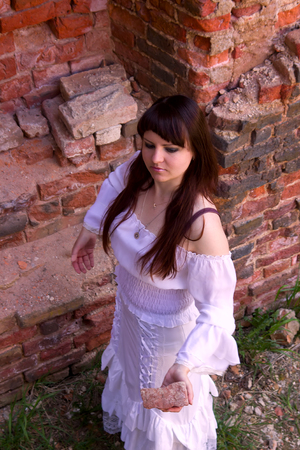 unconcerned: Girl in old-fashioned white dress among ruins of old manor. importance of spirit of parent of roots of noble descendant