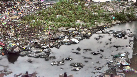 contaminacion del agua: La contaminación de plástico en la naturaleza. Basura y botellas que flotan en el agua. Contaminación ambiental. Basura en el agua del río.