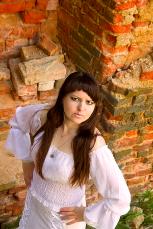 impassioned: Girl in old-fashioned white dress among ruins of old manor. Looks to be the hostess