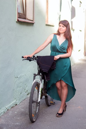 ours: The perfect outfit! Advertising slogan: On ours bikes you can ride even in evening dress. Model pose for photograph Stock Photo