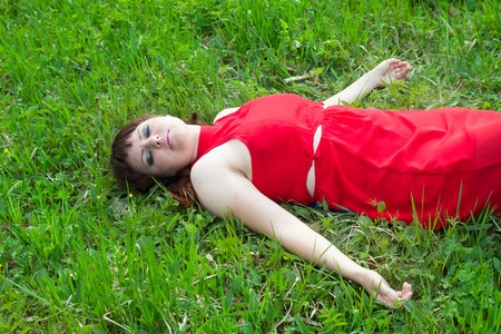 leisure and people concept - young girl in red lying on grass Stock Photo