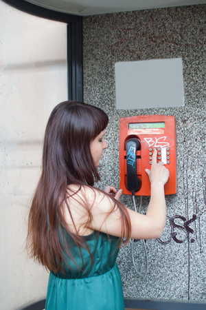 girl and vintage telephone booth. outdated method of communication between people Stock Photo