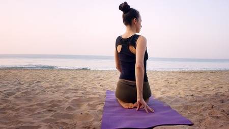 outdoor on beach girls yoga trainer at home yoga. ahead of the ocean around exotic India Stock Photo