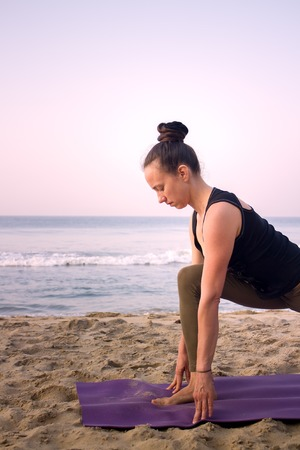 asana: outdoor on beach girl yoga trainer at home yoga. ahead of the ocean around exotic India Stock Photo