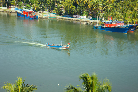battleship: Water transport of India. Passenger flat-bottomed boat under canopy and two moored boats (small) move along canal surrounded by palm trees Stock Photo