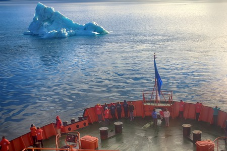 Franz-Joseph Land - 10 July 2016: Tourist cruise in high Arctic. Ship sails close to small iceberg. But we should remember that 90% of ice mountain is under water. Titanic Iceberg was a little more Stok Fotoğraf - 76377793