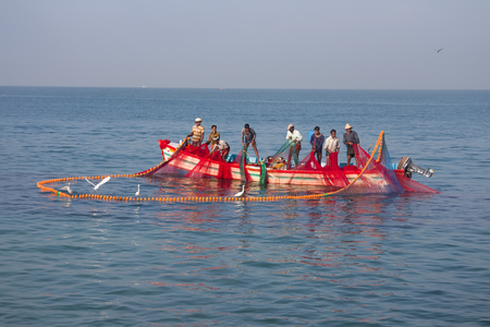 India, Kerala - December 27, 2015: Indian fishermen graphically pull painted Seine right in boat 2. Net painted in bright colors, flying terns, wooden boat. Heard Hindu hymns Editorial