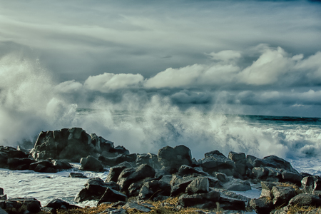 turbulent waves of Pacific ocean and rugged beauty of basalt rocks. Dead swell