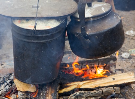 outdoor fireplace: soup on camping fire. food in pot in recreation