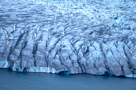 calved: Harsh glaciers of Arctic. Live glacier: front wall and icefall (recently calved ice block in ablation zone). Novaya Zemlya archipelago, North island. View from helicopter