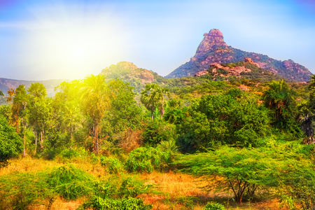single mountain in India at sunset. bright warm Golden landscape Stock Photo